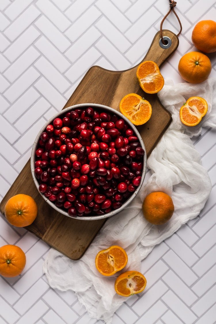 Ingredients for Cranberry Clementine sauce on a wooden board