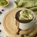 Matcha Hot Chocolate Recipe up close with whipped cream on a wooden board