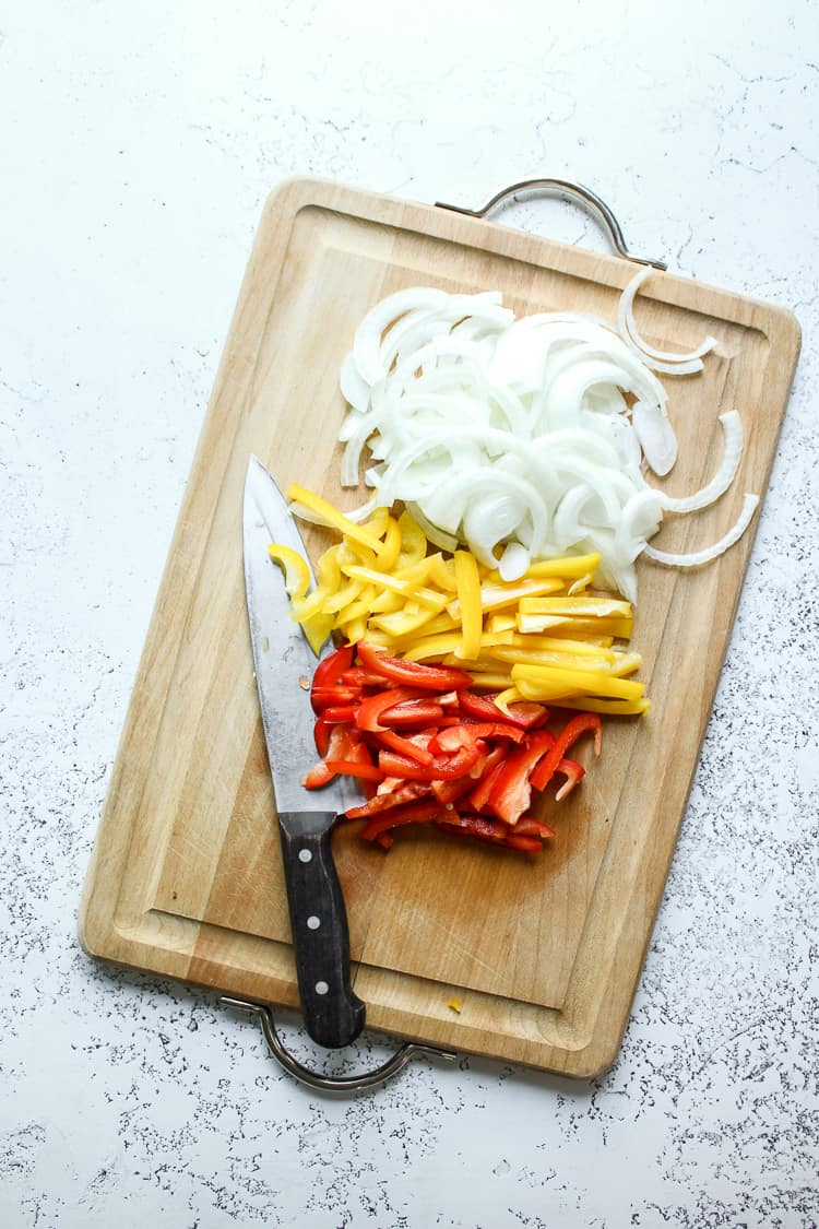 Chopped bell peppers and onion on a chopping board for fajita bowls