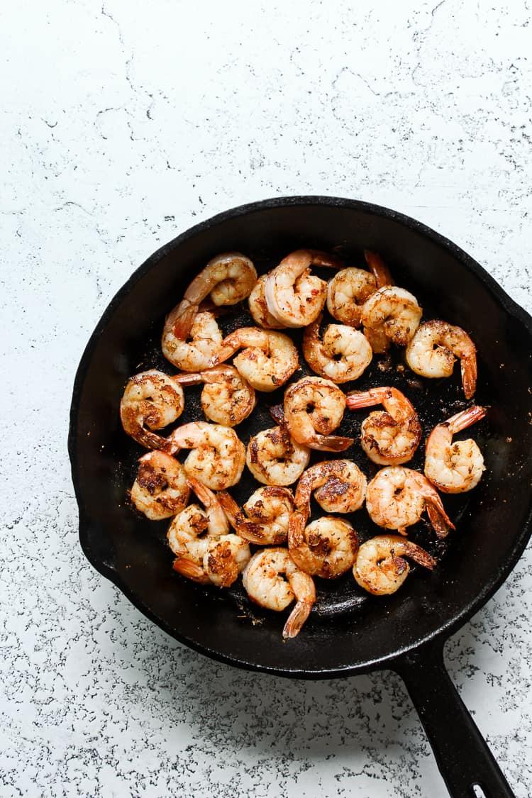 Sauteed shrimp in a cast iron skillet for fajita bowls