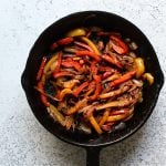 Sauteed fajita vegetables in a cast iron skillet for fajita bowls