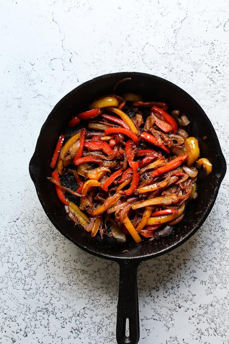 Sauteed fajita vegetables in a cast iron skillet for fajita bowls