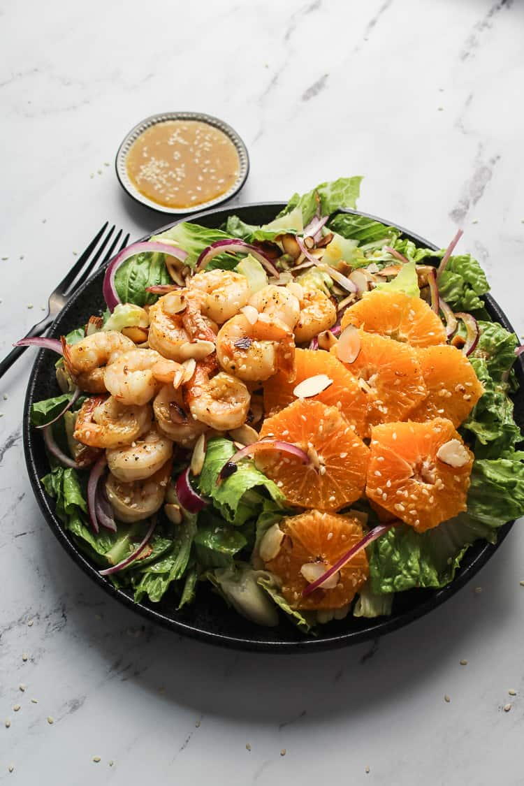 Shrimp Salad on a plate with oranges and red onions