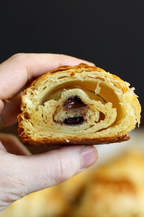 chocolate croissant cut in half in hand