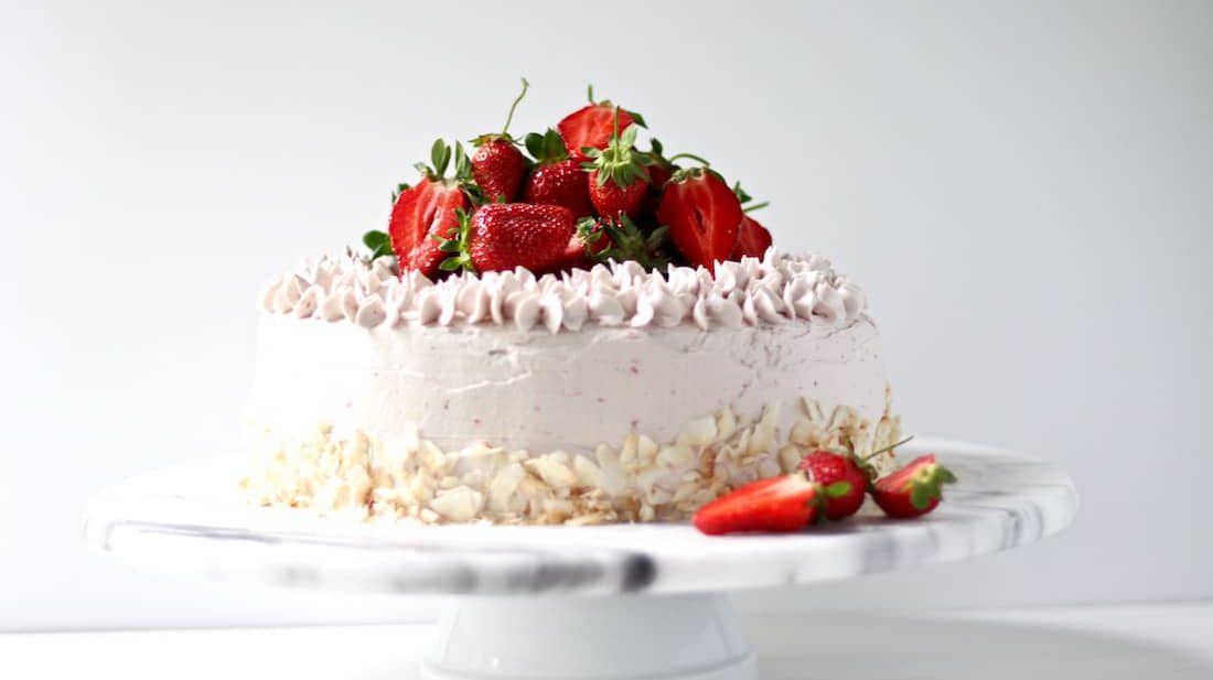 Gluten free strawberry cake on a marble cake stand