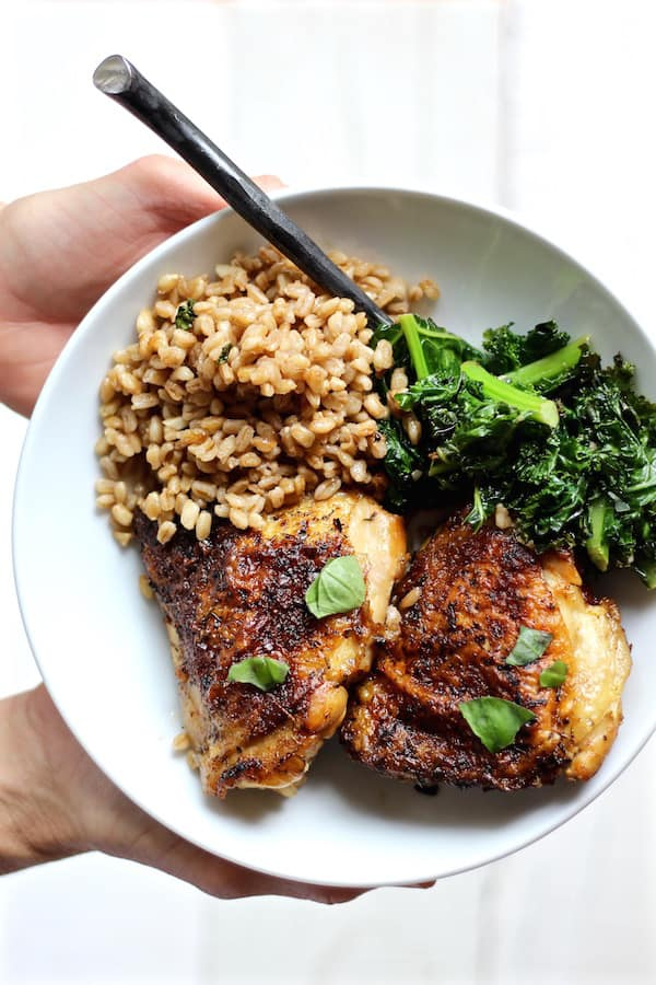 crispy chicken kale farro salad plated with hands