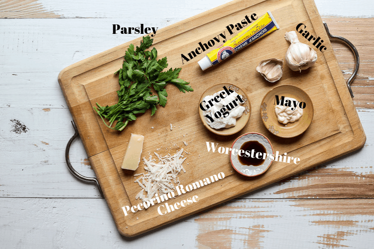 Healthy Caesar dressing ingredients on a wooden cutting board