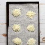 Shredded pecorino Romano crisps on a baking sheet
