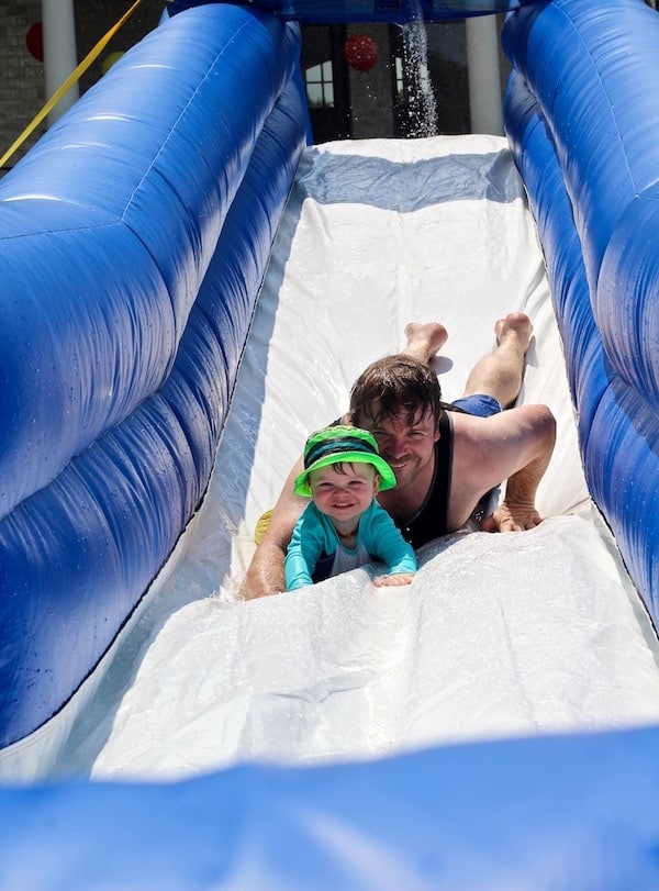 Dad and son sliding down water slide