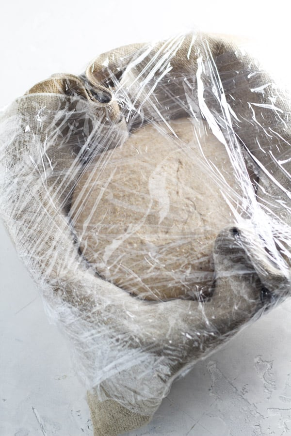 Sourdough honey splet bread covered in plastic wrap