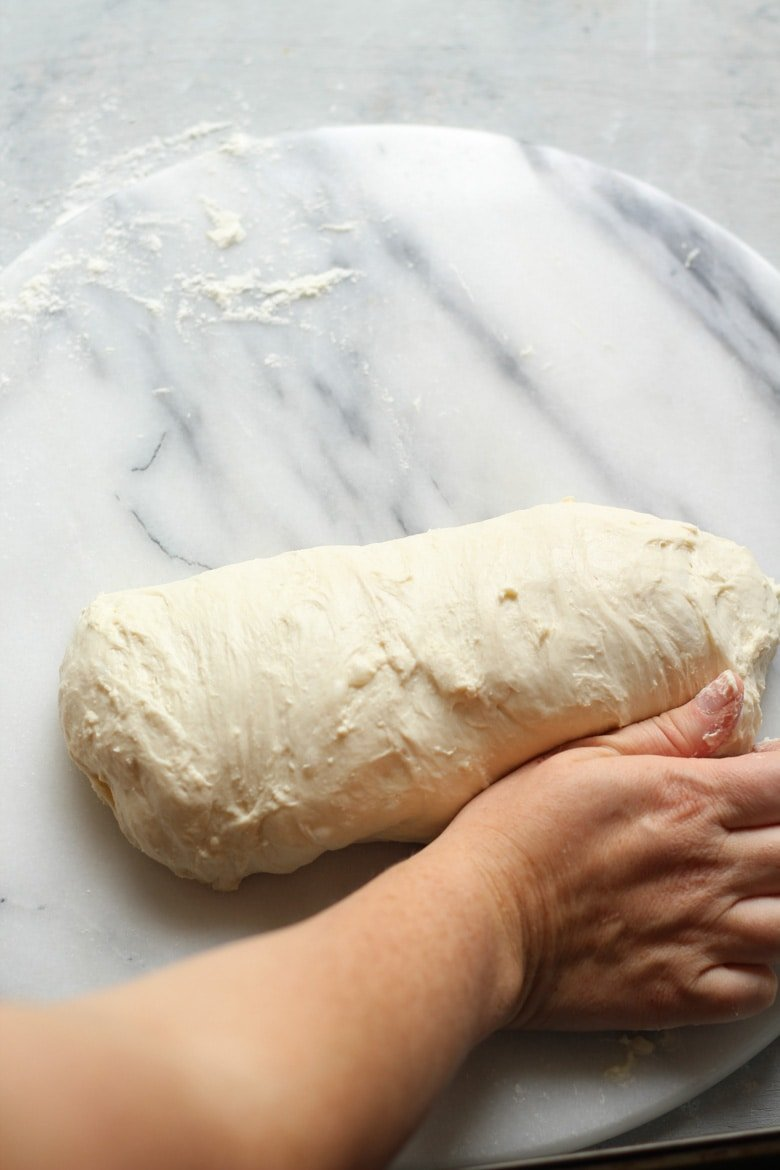 Shaping sourdough bread dough in a log or batard for a loaf tin