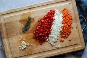 Red pepper, onions, carrots, garlic, and herbs chopped for chicken meatball soup