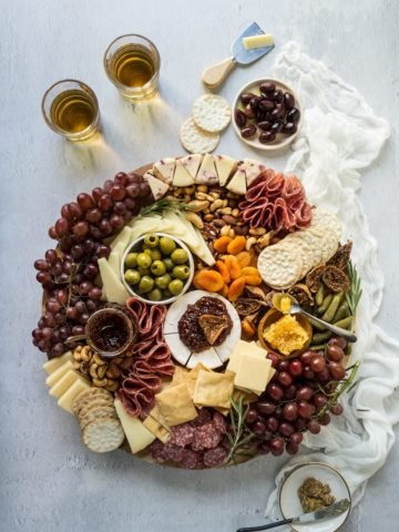 A charcuterie cheese board on a wooden board with a linen napkin