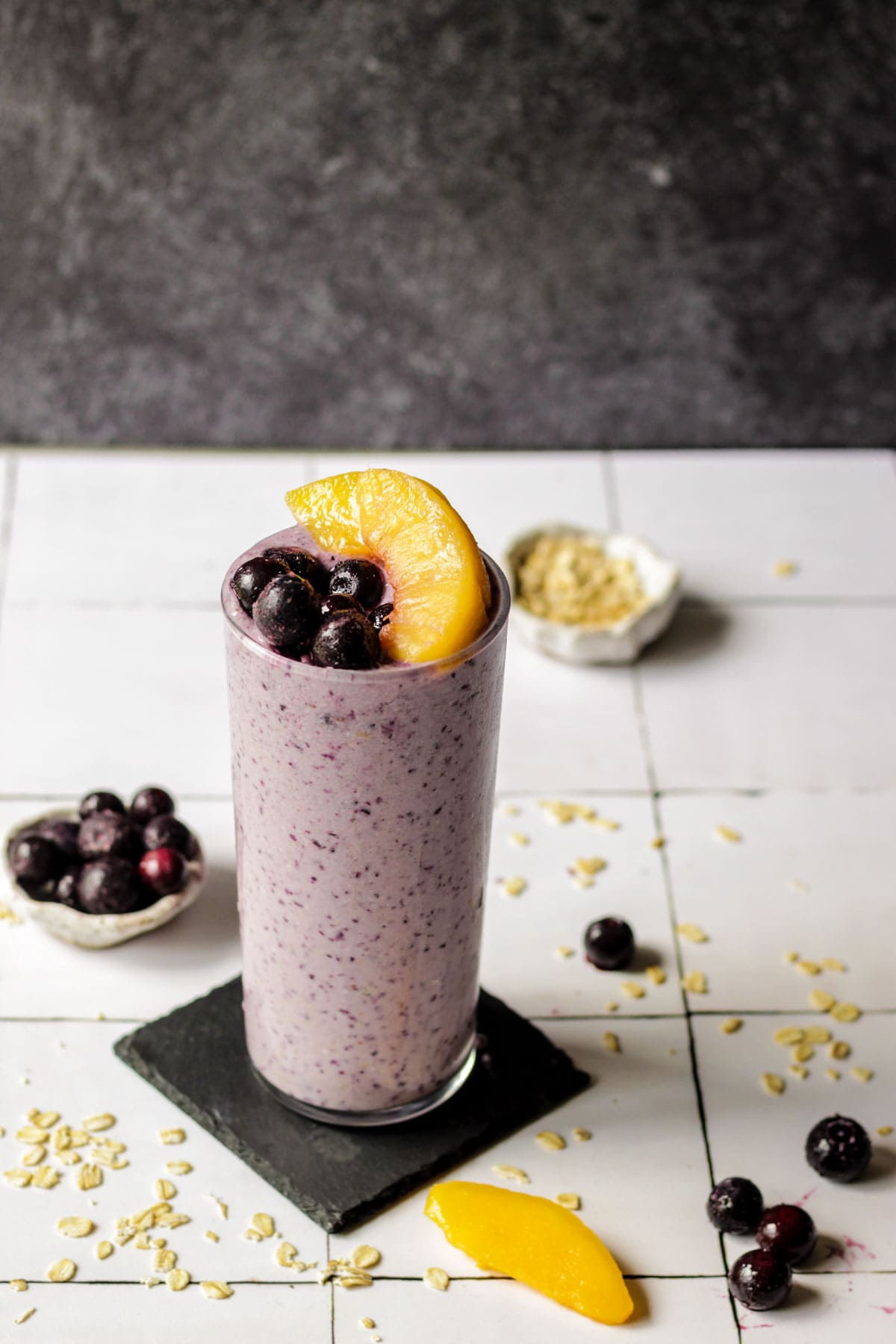 A glass of blueberry peach oatmeal smoothie with bowls of blueberries and peaches