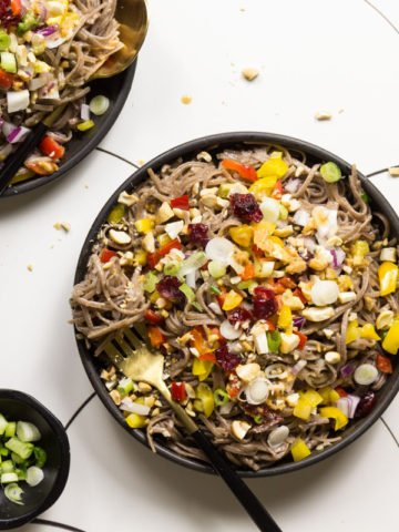 Cold Soba Noodle Salad on black plates with black cutlery