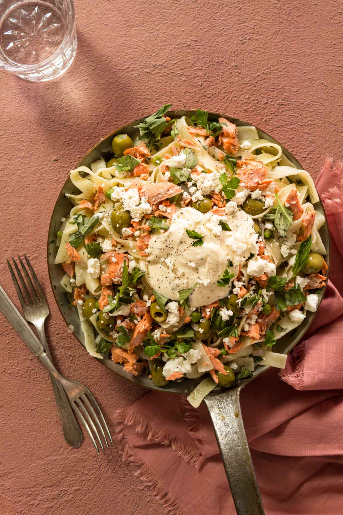 Salmon pasta with creme fraiche in a skillet with forks