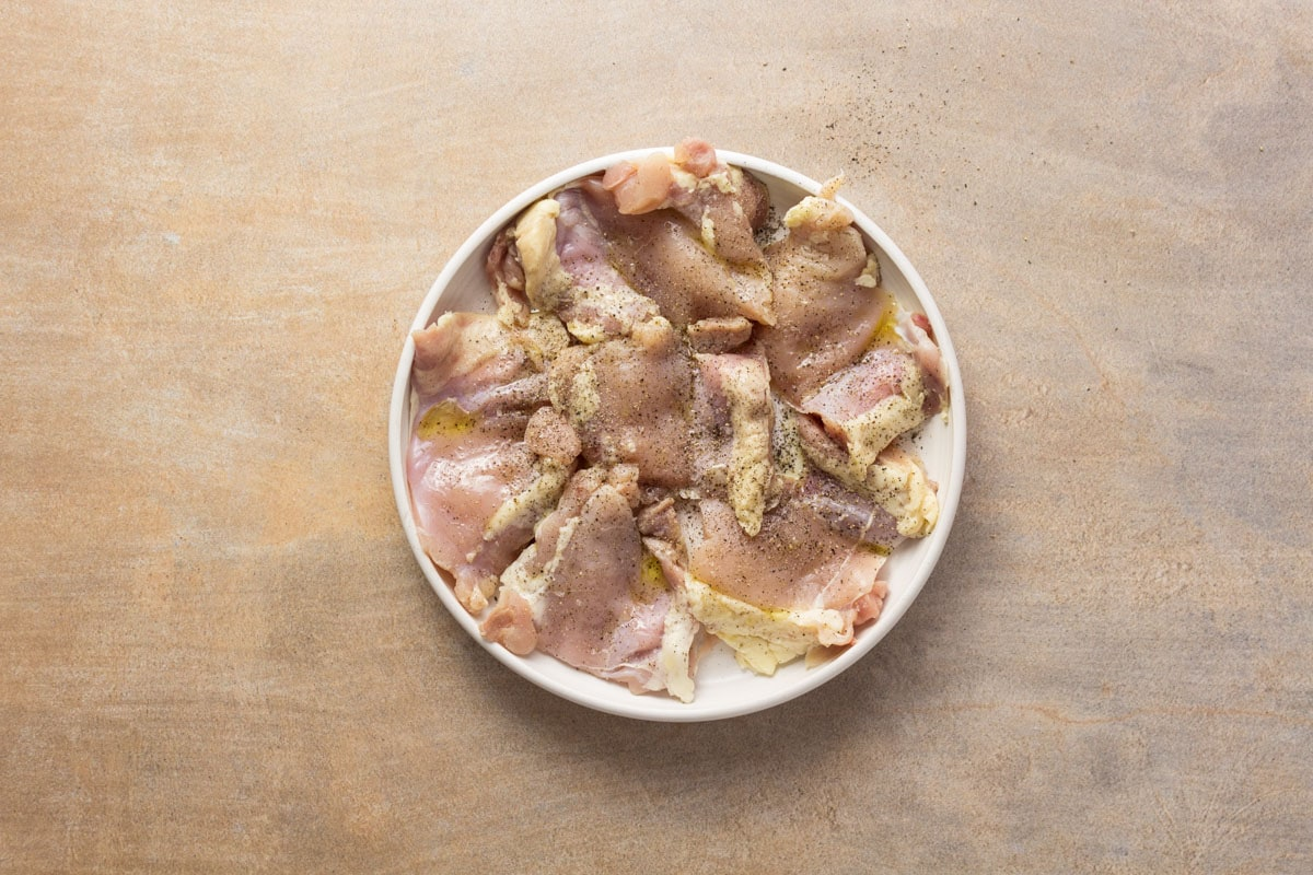uncooked Chicken thighs on a white plate