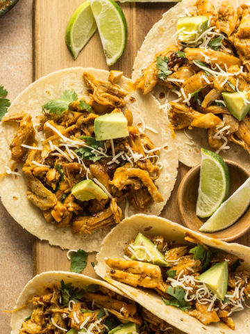 Chipotle orange tacos on a cutting board with limes