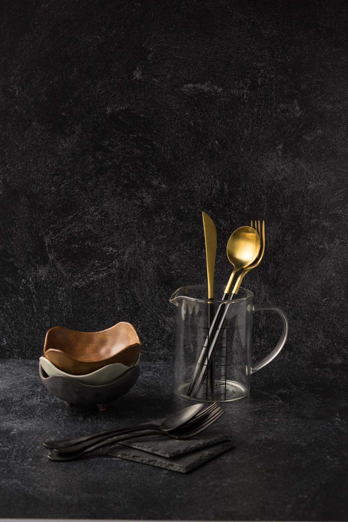 Gold and black spoons in a glass