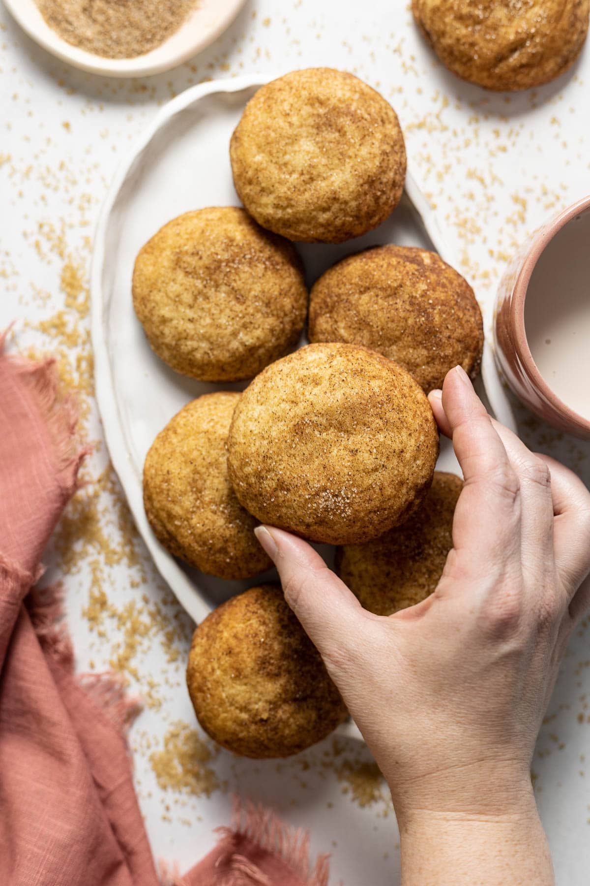 Chai snickerdoodle cookies held in a hand on a plate