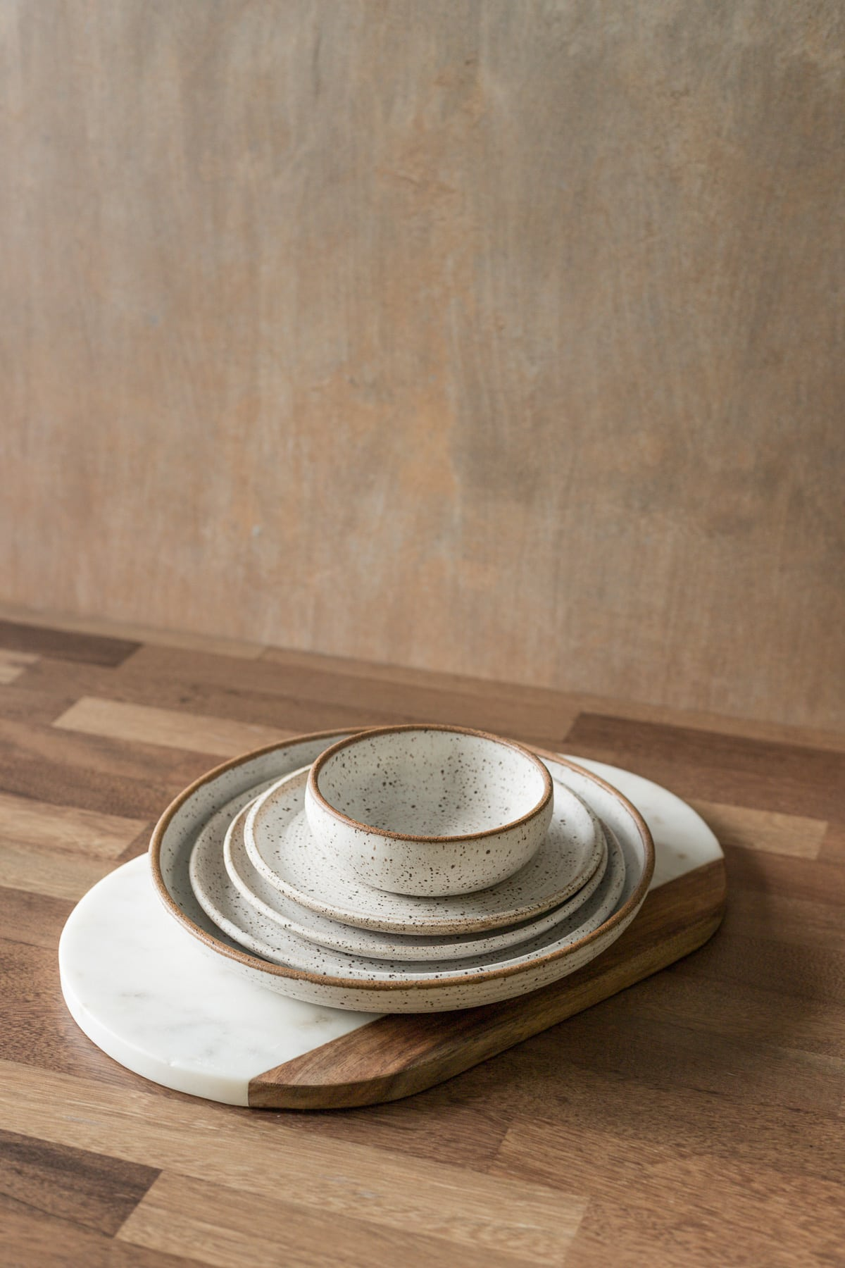Pottery plate and bowls stacked on a marble cutting board