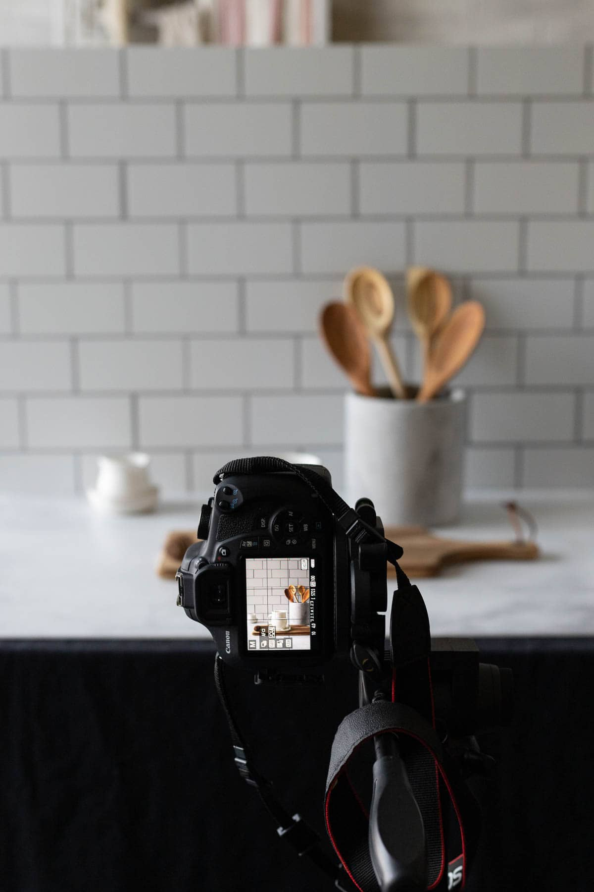A camera taking a picture with a kitchen canister and subway tile backdrop