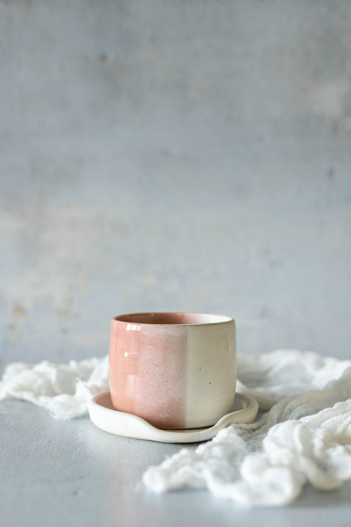Pink pottery cup with linen cloth