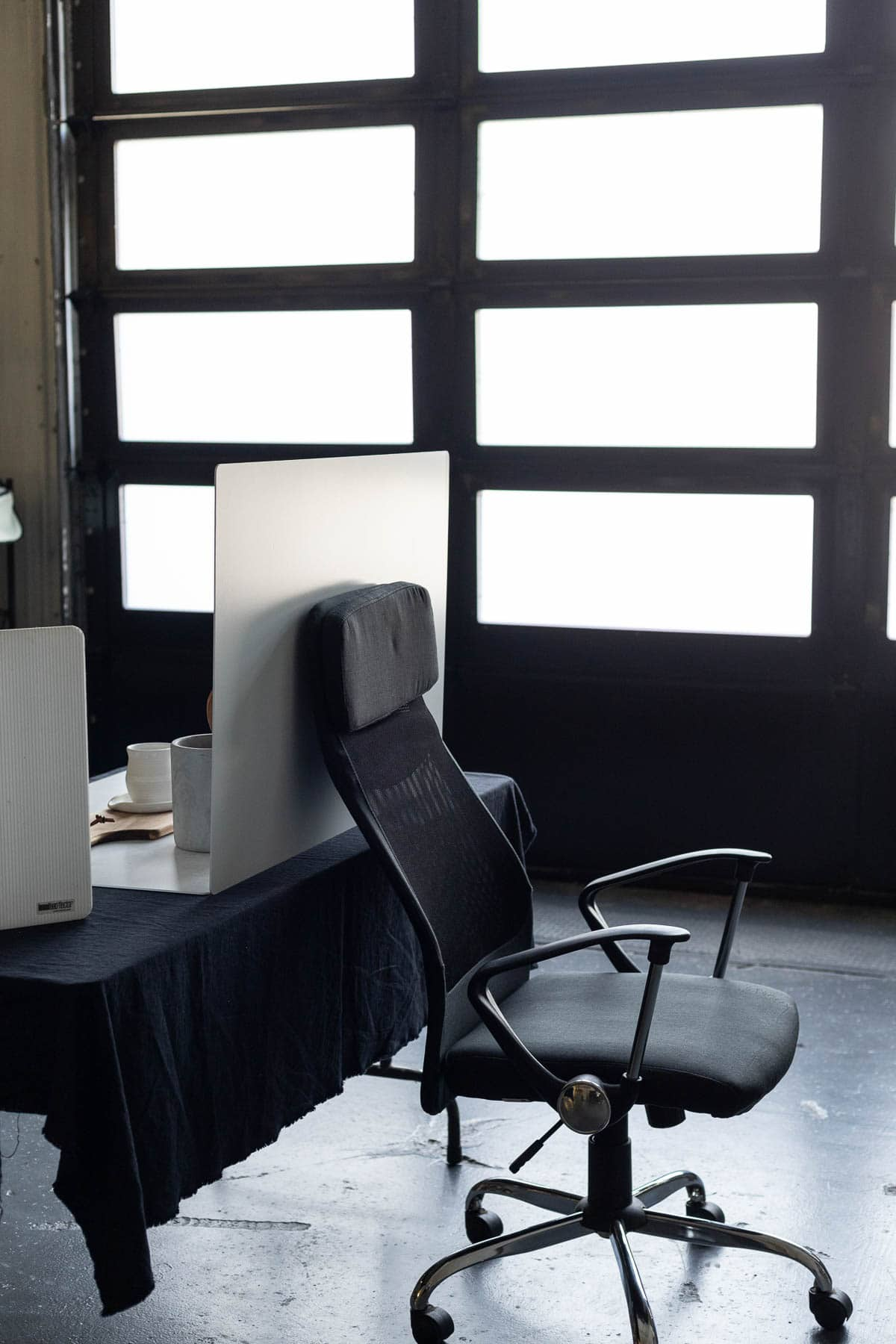 An office chair holding up a photography backdrop