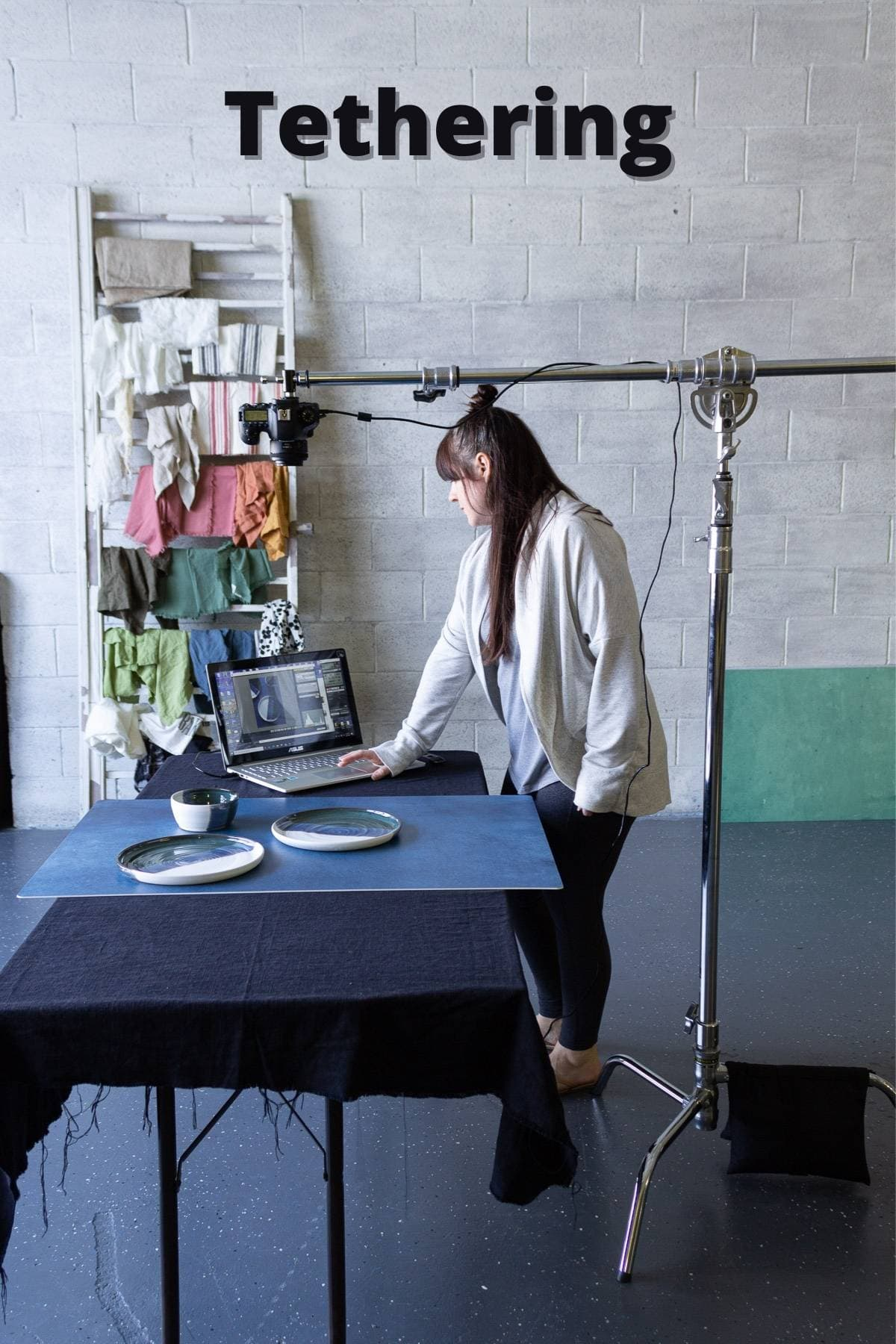 A person standing by a computer with a c-stand