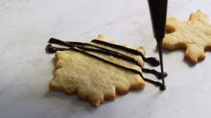 drizzling chocolate over shortbread cookie