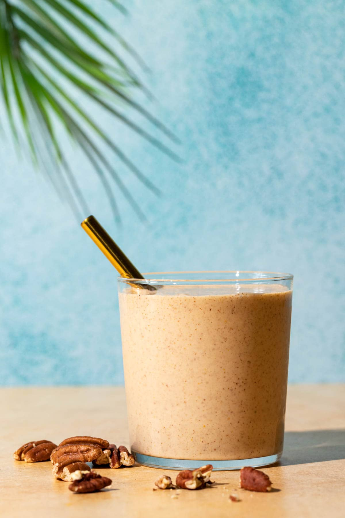 Banana Bread smoothie with crushed toasted pecans in front on a blue and yellow background