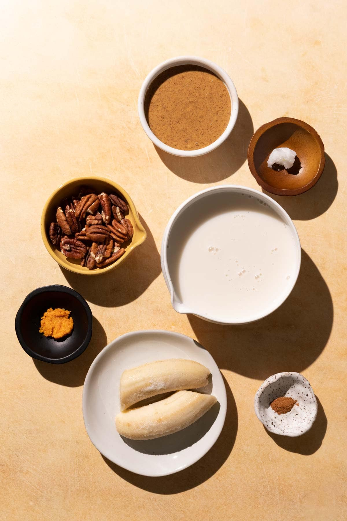 Ingredients for Banana Bread smoothie in bowls on a yellow background