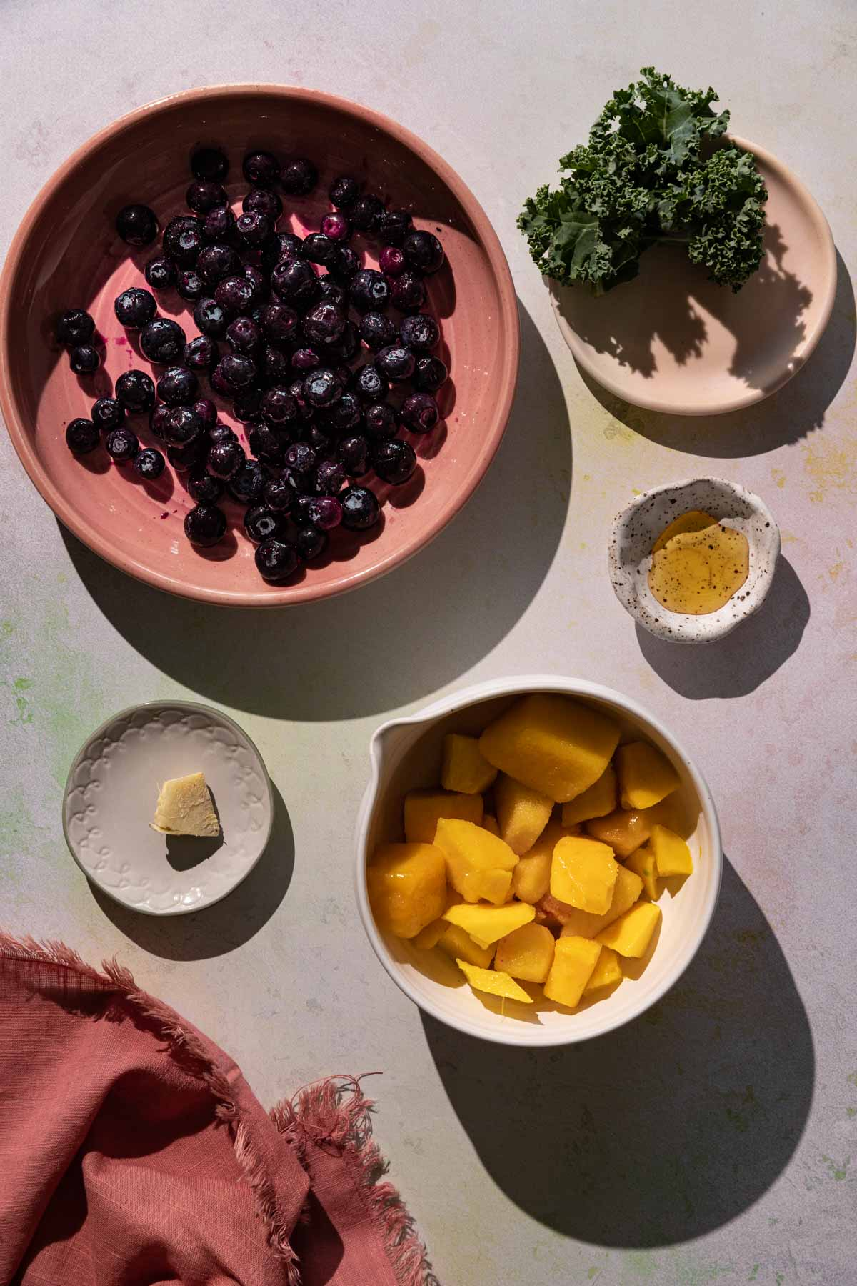Ingredients for Blueberry Kale smoothie in bowls on a colorful background with a red linen cloth