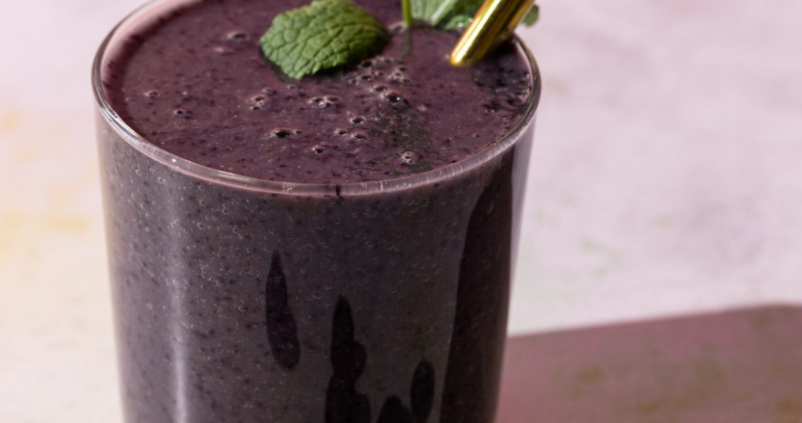 Blueberry Kale smoothie with mint and blueberries on a colorful background