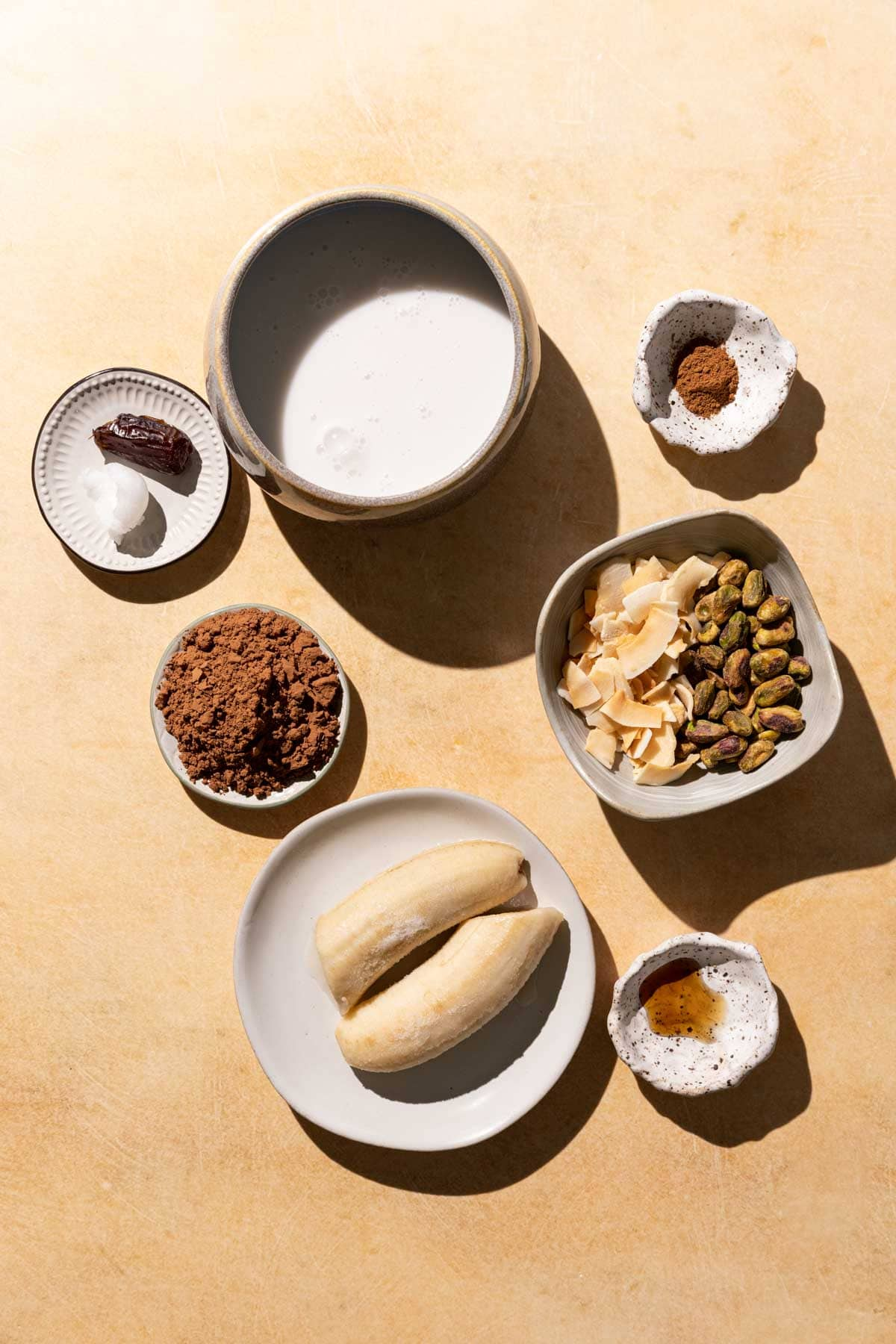 Ingredients for Chocolate Coconut smoothie in bowls on a yellow background