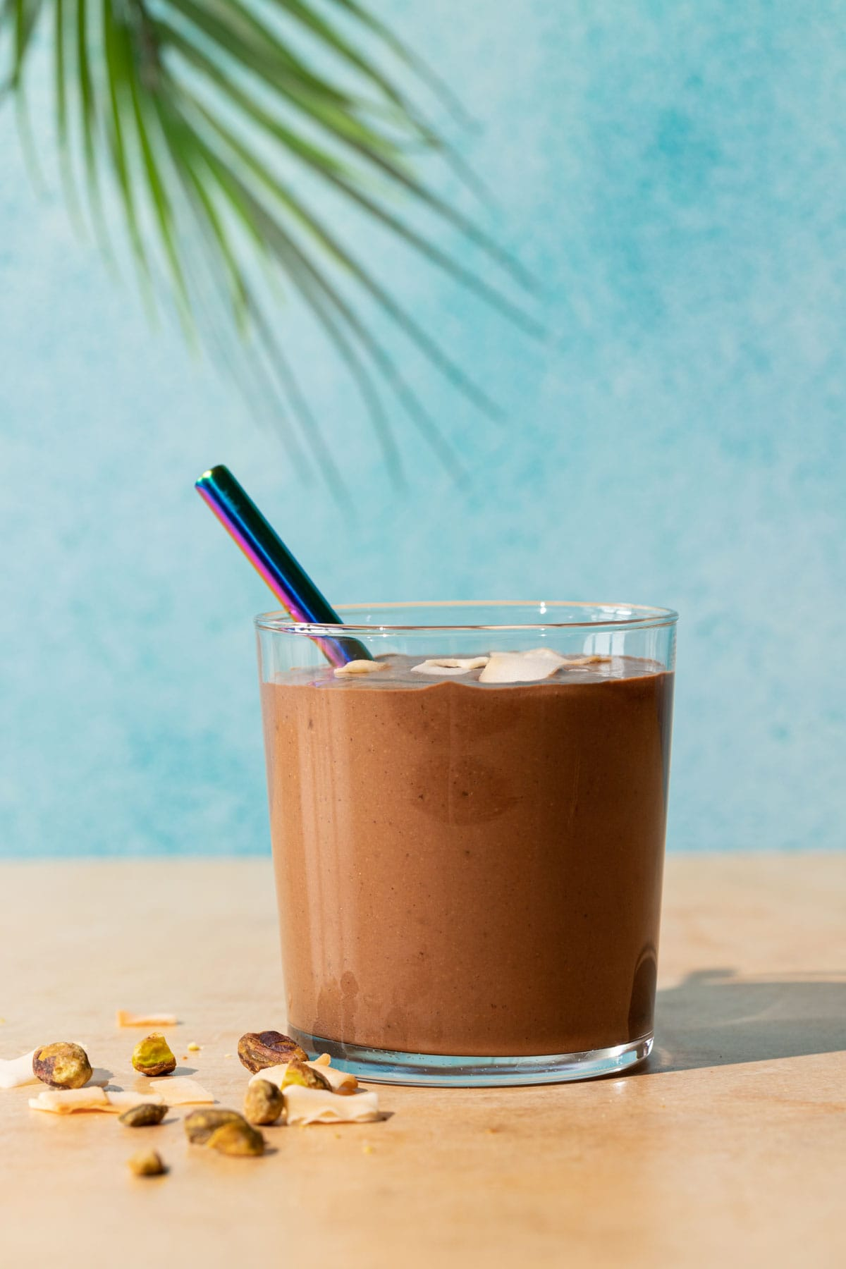 Chocolate Coconut smoothie with toasted coconut chips and pistachios on a yellow and blue background with palm leaf in background