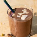 Chocolate coconut smoothie with toasted coconut chips and pistachios on a yellow background