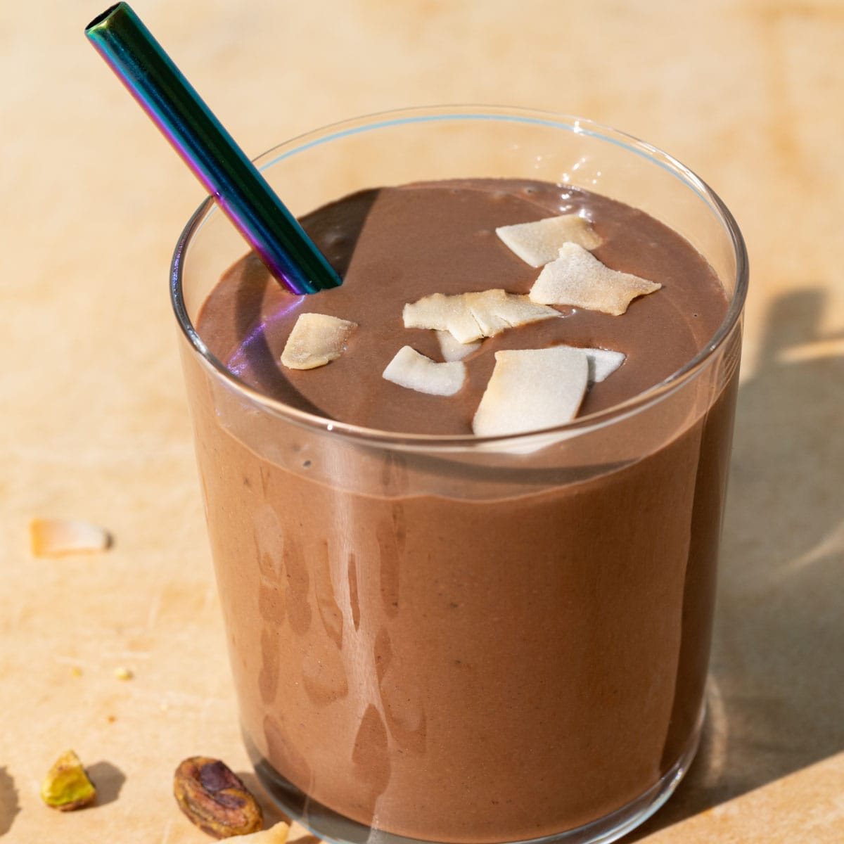 Close up of chocolate coconut smoothie with toasted coconut chips on a yellow background