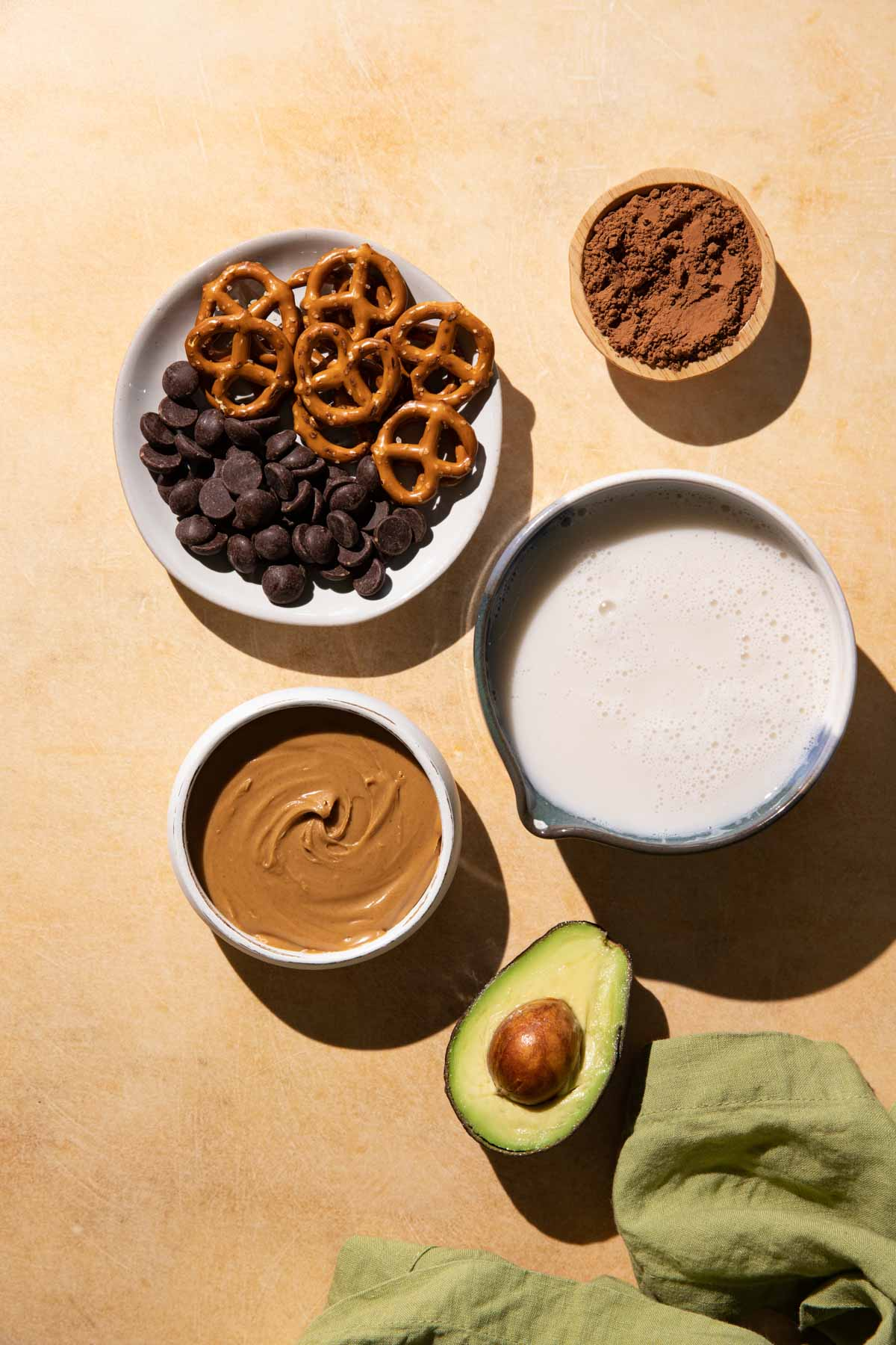 Ingredients for Chocolate Peanut Butter Smoothie in bowls on a yellow background with a green linen cloth