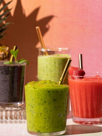 Fruit smoothies in four glasses with straws