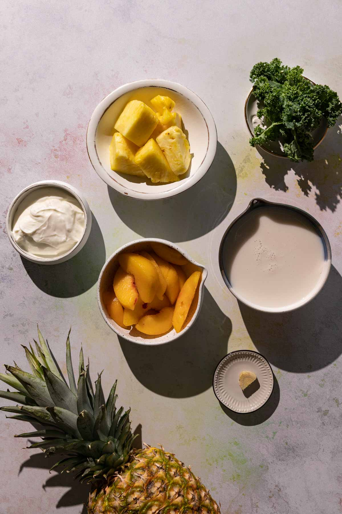 Ingredients for Pineapple Peach smoothie in bowls on a colorful background with whole pineapple