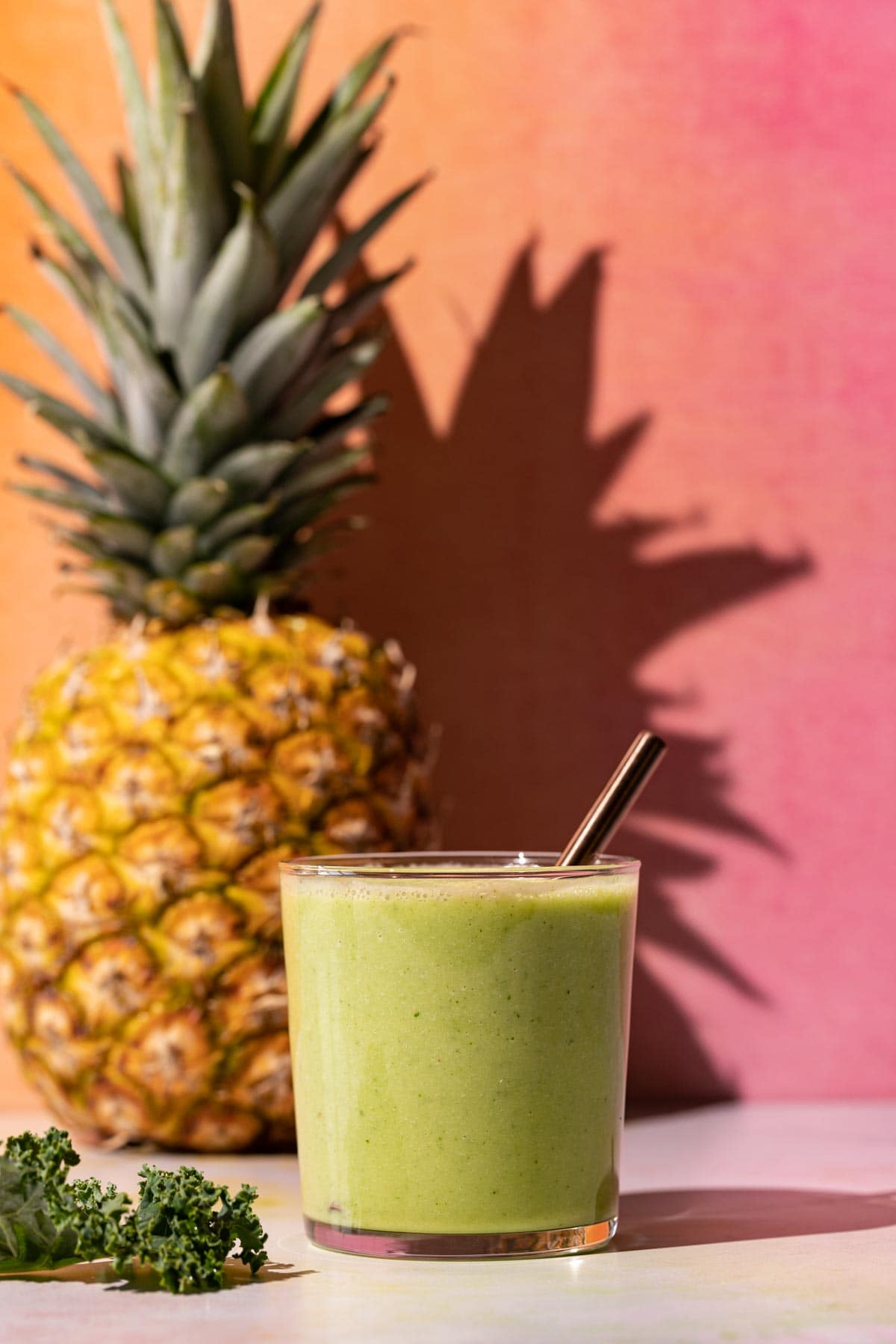 Pineapple Peach smoothie on a colorful background with whole pineapple and kale