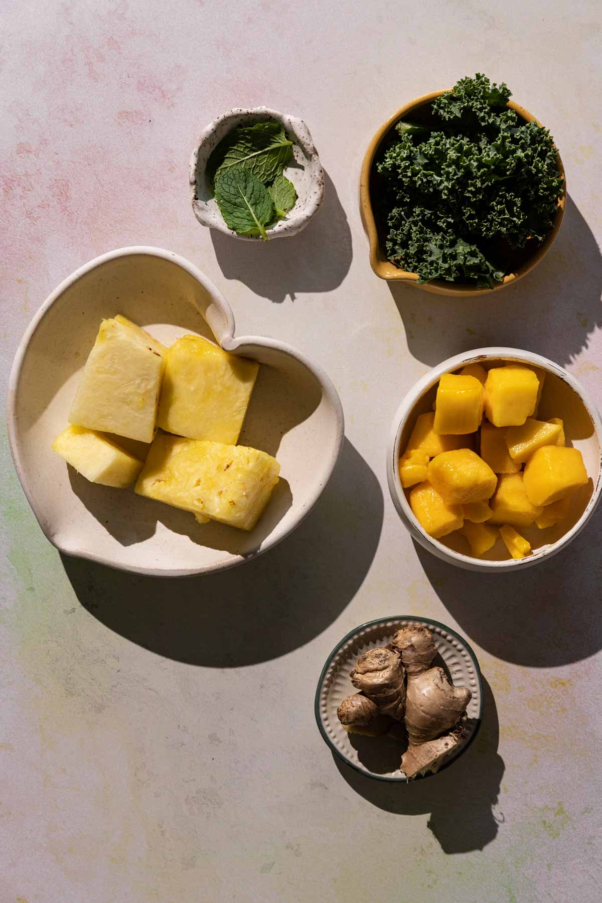 Ingredients for Mango Pineapple Kale smoothie in bowls on a colorful background