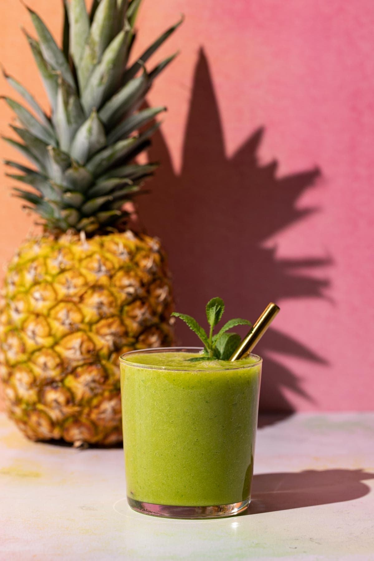 Mango Pineapple Kale smoothie on a colorful background with a pineapple
