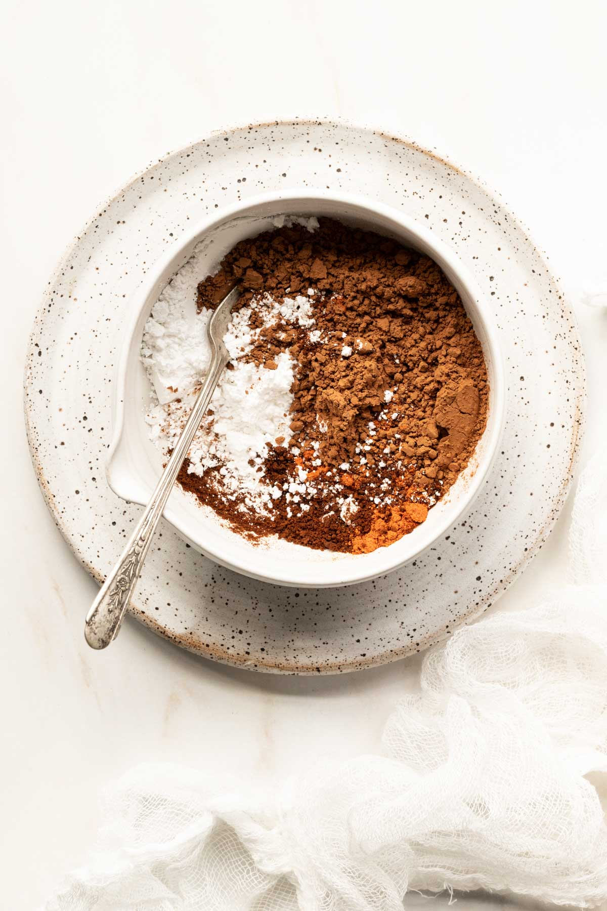 Cocoa powder and powdered sugar in a clay bowl with a spoon