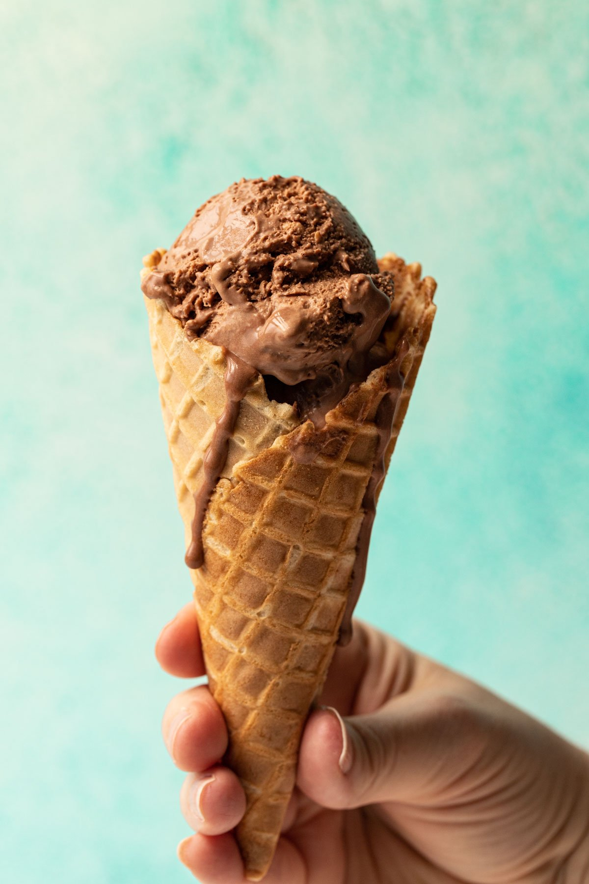 Chocolate no churn ice cream in a waffle cone held in a hand