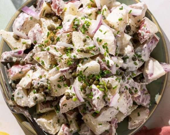 Potato salad with capers on a green plate