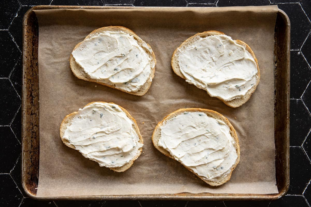 Goat cheese spread on slices of toast on a sheet pan