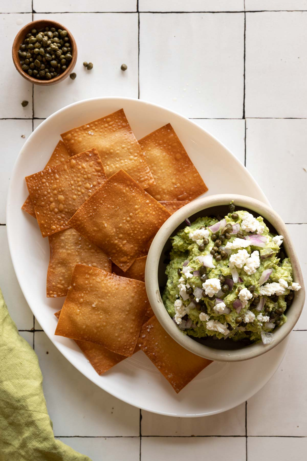 Wonton skins and a bowl of goat cheese guacamole on a plate