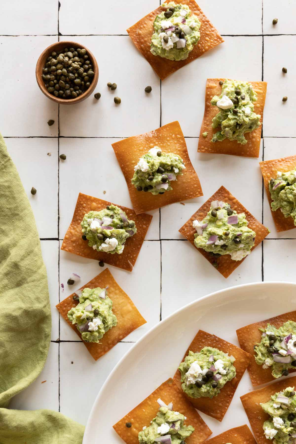 Wonton skins topped with guacamole on a plate